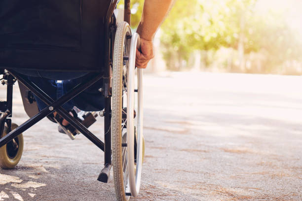 Closeup photo of Young disabled man holding wheelchair outside in nature stock photo