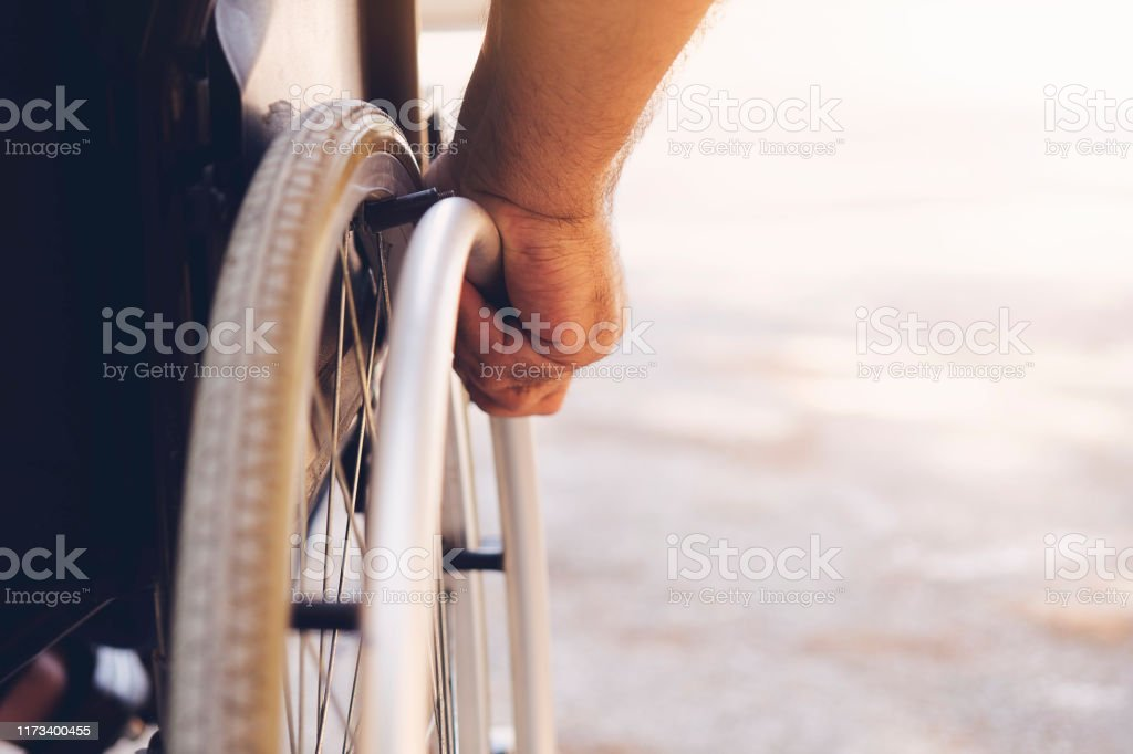 Closeup photo of Young disabled man holding wheelchair outside in nature - Royalty-free Acessibilidade Foto de stock