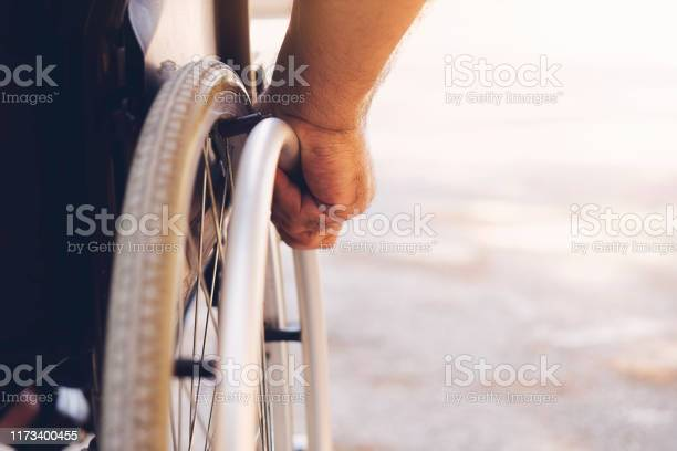 Closeup Photo Of Young Disabled Man Holding Wheelchair Outside In Nature - Fotografias de stock e mais imagens de Acessibilidade
