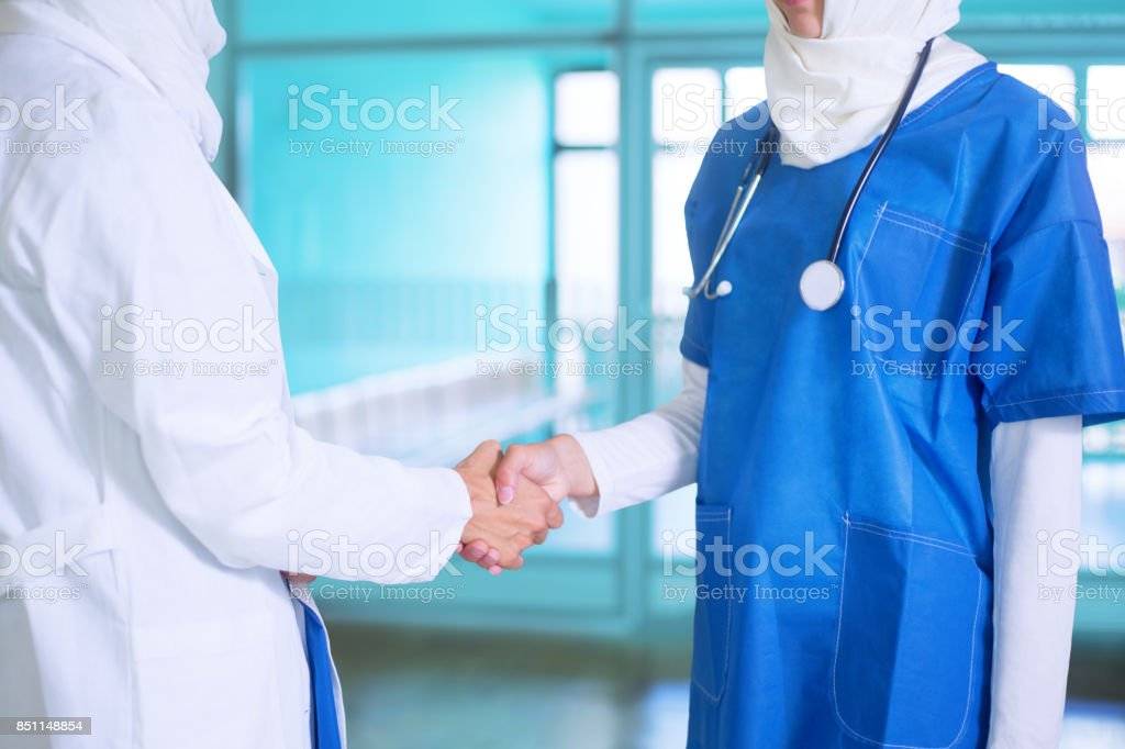 Close-up photo of young female arabic doctor and a nurse  white and blue medical uniform and a white hijab shaking hands stock photo