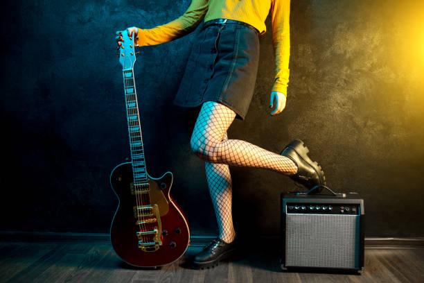 nahaufnahme von jungen hipster-frauen beine und rote gitarre in neonlicht. rockmusiker spielt elektrische gitarre. 90er-jahre-konzept. - bands der 90er stock-fotos und bilder