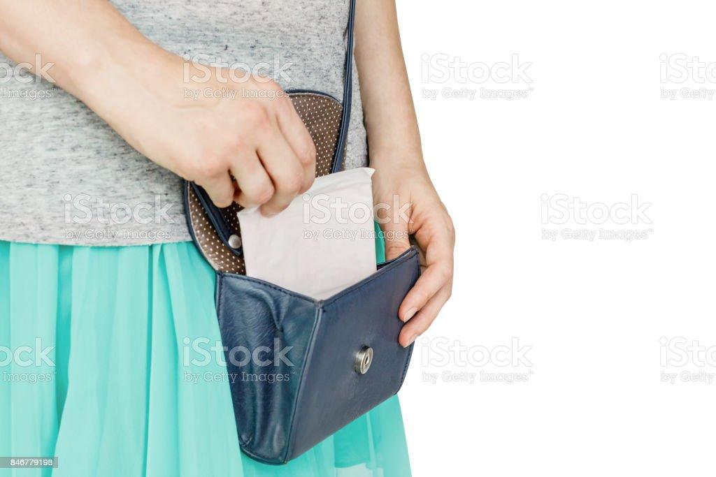 Closeup photo of young stylish woman putting hygiene pad in handbag stock photo
