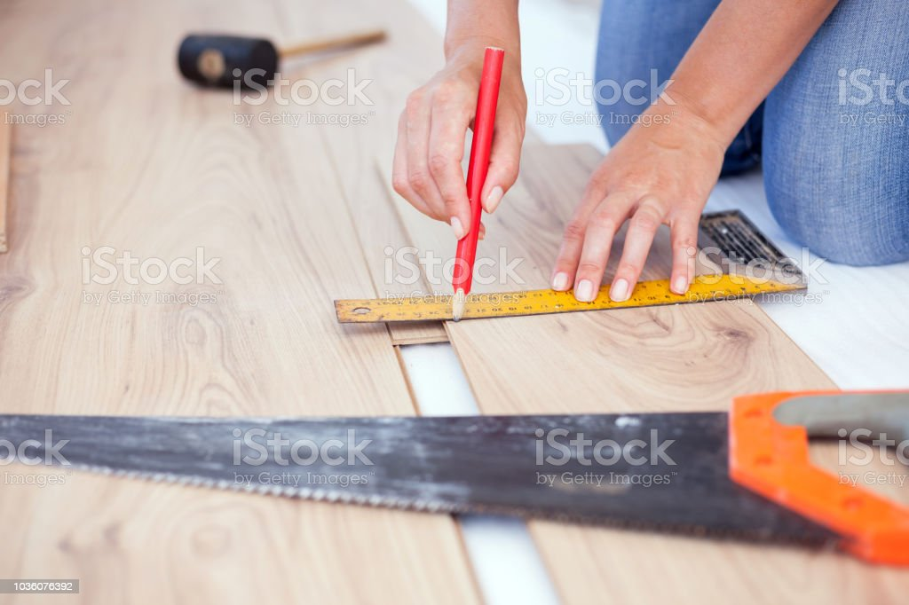 Close Up Photo Of Young Woman Measuring And Marking Laminate Floor Tile Installing