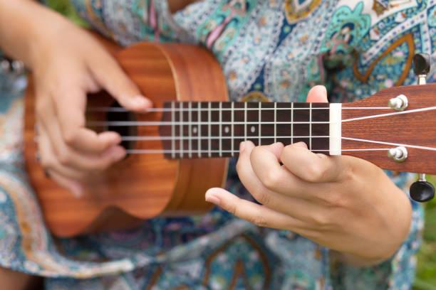 Closeup photo of young woman playing on Ukulel. stock photo