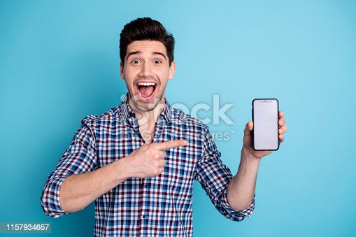 istock Closeup photo portrait of astonished wondered mad laughing ecstatic freelancer holding new developing updating his telephone isolated pastel background 1157934657