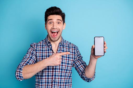 istock Closeup photo portrait of astonished wondered mad laughing ecstatic freelancer holding new developing updating his telephone isolated pastel background 1157934657