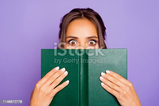 Close-up photo portrait of pretty sweet lovely smart clever cute wondered charming bookworm closing covering face with notebook notepad holding hands isolated violet background.