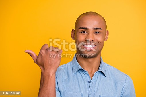 1163696387 istock photo Close-up photo portrait shot headshot of handsome attractive nice glad optimistic millennial gesturing to copy empty blank space near shoulder isolated bright background 1163696348