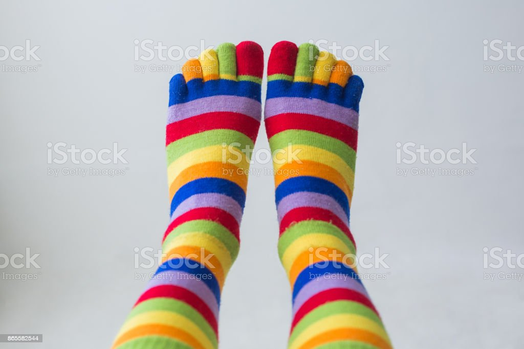 Close-up photo woman's feet in multi color socks stock photo