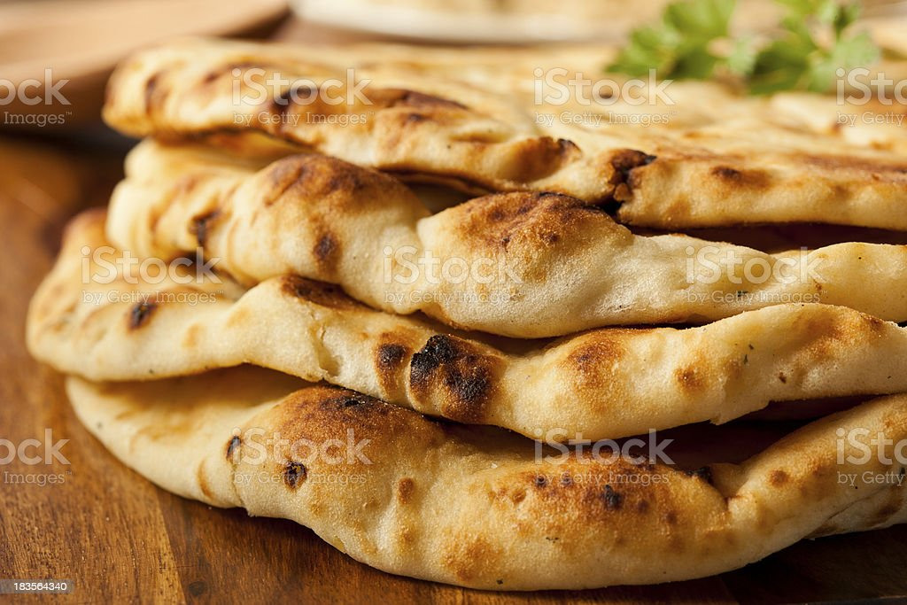 Close-up photograph of a pile of plain naan flatbreads stock photo