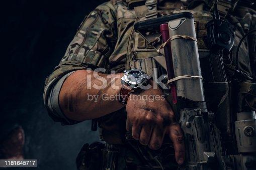 Closeup photo shoot of man's hand holding machine gun. Man is wearing military uniform and wach.
