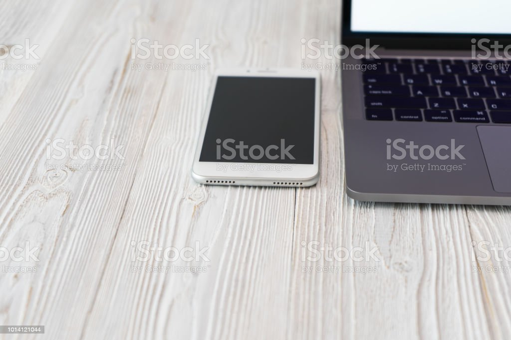Close-up picture of a keyboard with a phone and computer laptop technology stock photo