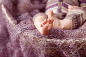 Closeup picture of newborn baby feet on knitted plaid. Beautiful conceptual image of Maternity