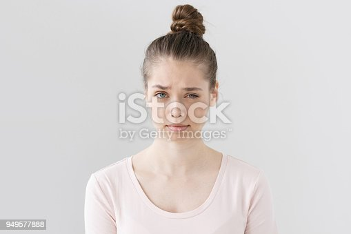 Closeup picture of nice young female without make up isolated on grey background raising eyebrow with vivid expression of suspicion, looking mistrustful towards she is hearing and looking at.