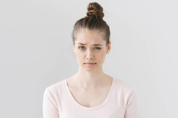 Closeup picture of nice young female without make up isolated on grey background raising eyebrow with vivid expression of suspicion, looking mistrustful towards she is hearing and looking at. stock photo