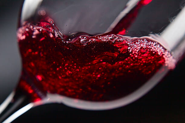 Close-up picture of red wine pouring on wine glass Red wine in wineglass on  black background merlot grape stock pictures, royalty-free photos & images