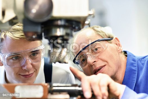 istock closeup picture: trainer and apprentice in vocational training on a milling machine - teacher explains details of the machine 942163690