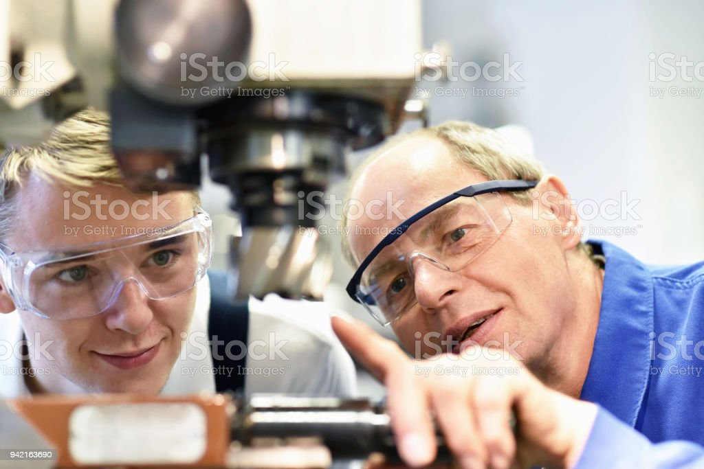 closeup picture: trainer and apprentice in vocational training on a milling machine - teacher explains details of the machine stock photo