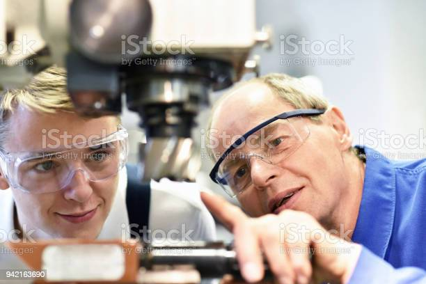 Closeup Picture Trainer And Apprentice In Vocational Training On A Milling Machine Teacher Explains Details Of The Machine Stock Photo - Download Image Now
