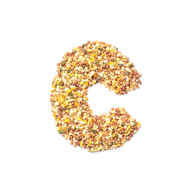 Closeup pile of cereal for bird food in C english alphabet isolated on white background stock photo