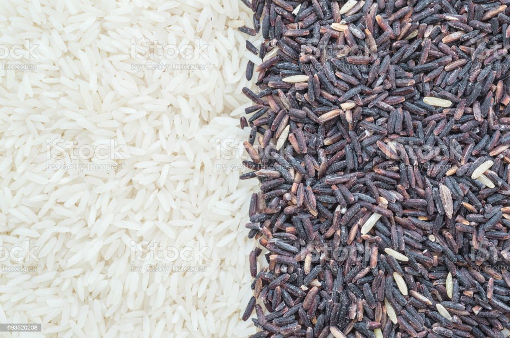 Closeup pile of mix rice by jasmine rice and riceberry rice textured background stock photo