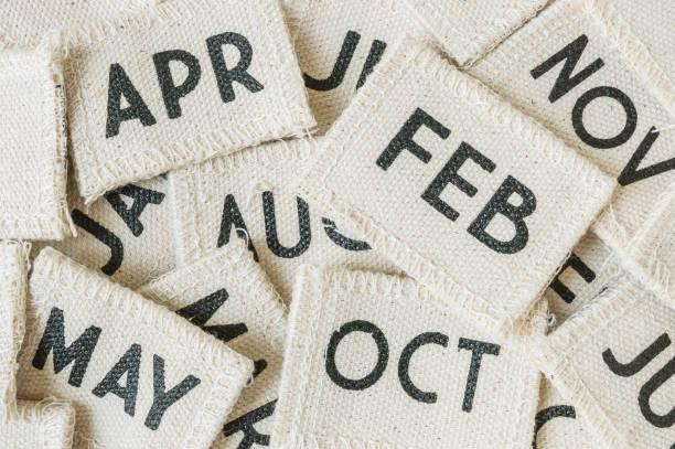 nahaufnahme aus kleinem stoffkalender in vielen monaten strukturierten hintergrund - kalender icon stock-fotos und bilder