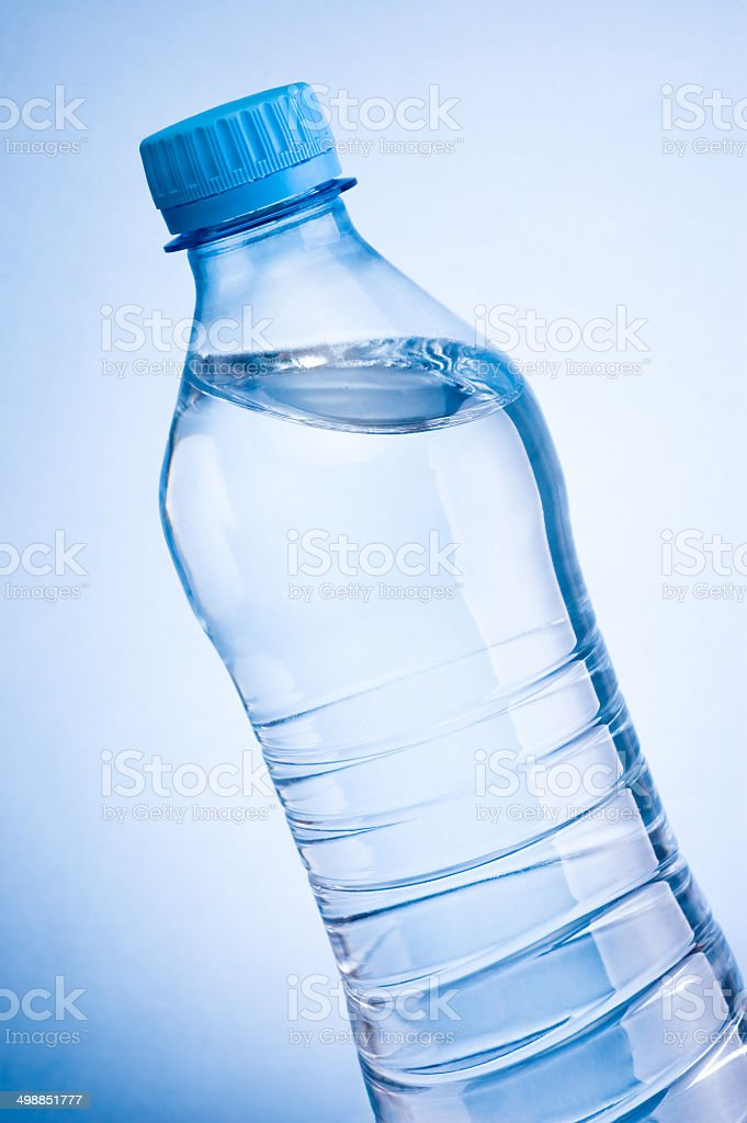 Close-up plastic bottle of drinking water obliquely on blue background stock photo