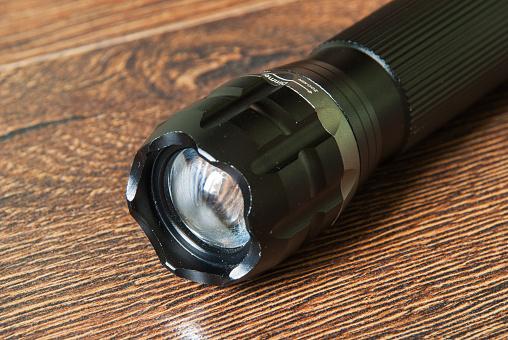 istock Closeup pocket LED flashlight on dark background. 1162552639