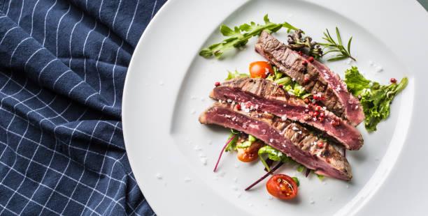 close-up teil saftige flanke steak vom salat salz pfeffer und rosmarin auf weißen teller. - flank steak marinaden stock-fotos und bilder