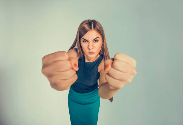 Closeup portrait angry young woman showing fists about to punch hit someone or to have nervous atomic breakdown isolated black background. Negative human emotions facial expression feelings attitude stock photo
