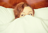 istock Closeup portrait attractive young shy woman lying in bed hiding under duvet blanket in a hotel room 673046442