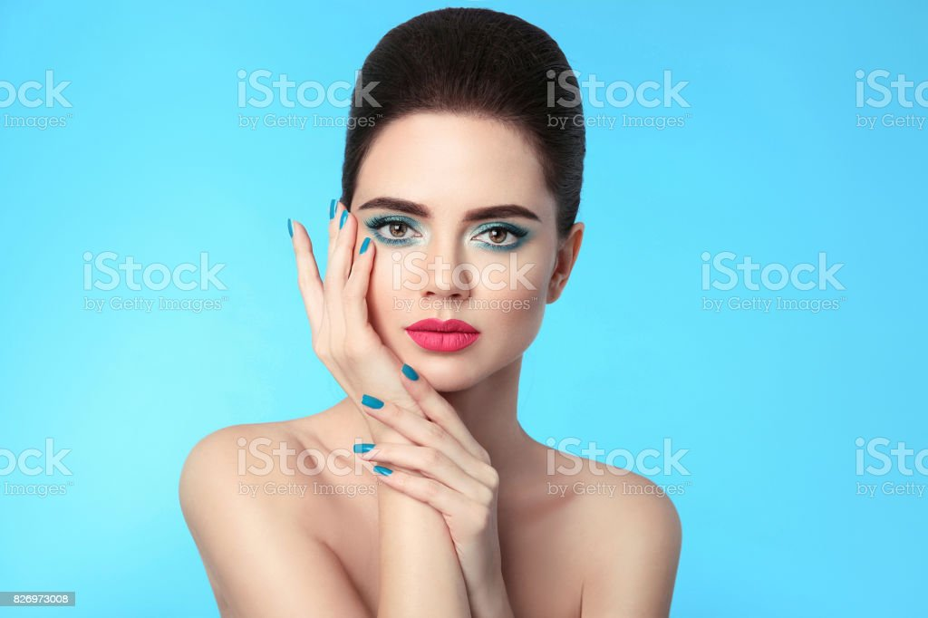 Closeup portrait beauty girl makeup. Manicured nails. Attractive young woman brunette with eye shadow and red matte lipstick isolated over blue background. stock photo