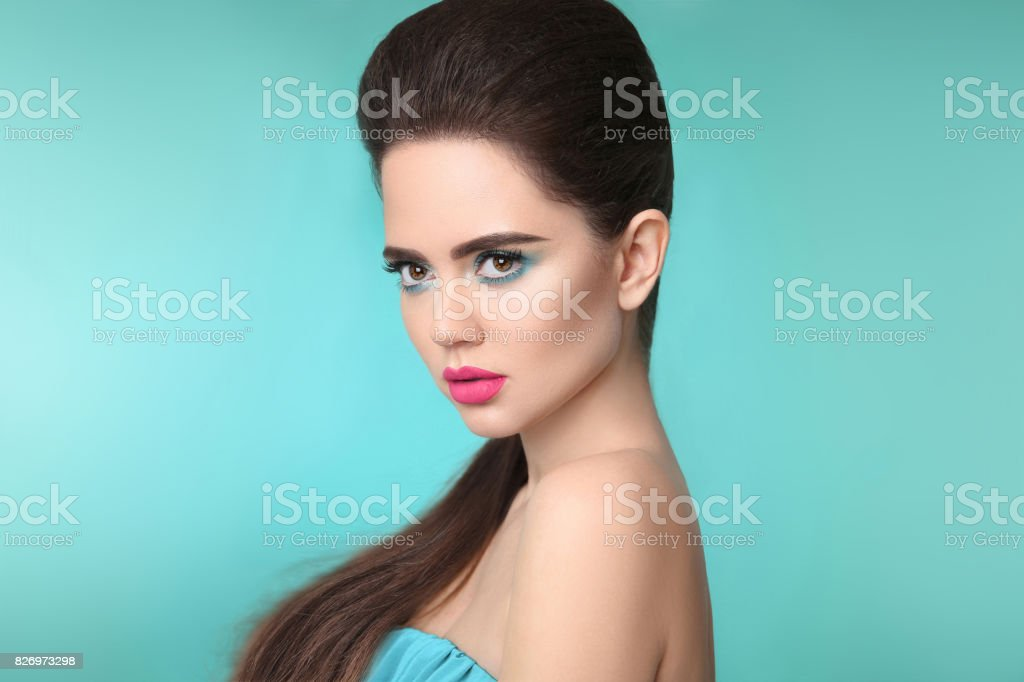 Closeup portrait beauty girl makeup. Matte lipstick. Beautiful fashion woman brunette with eye shadow and pink lips isolated over turquoise background. stock photo