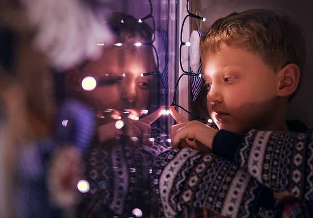 Cтоковое фото Крупным планом Портрет мальчика, сидя на окна с рождественский Lights