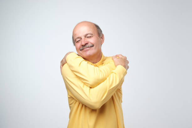 closeup portrait confident smiling man hugging himself. i am the best concept. - one man only stock pictures, royalty-free photos & images