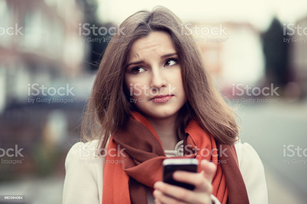 Closeup portrait funny sad young girl looking up thinking seeing bad news sms comment trolling message photos phone in hands disgusting emotion on face isolated cityscape background. Human expression ストックフォト