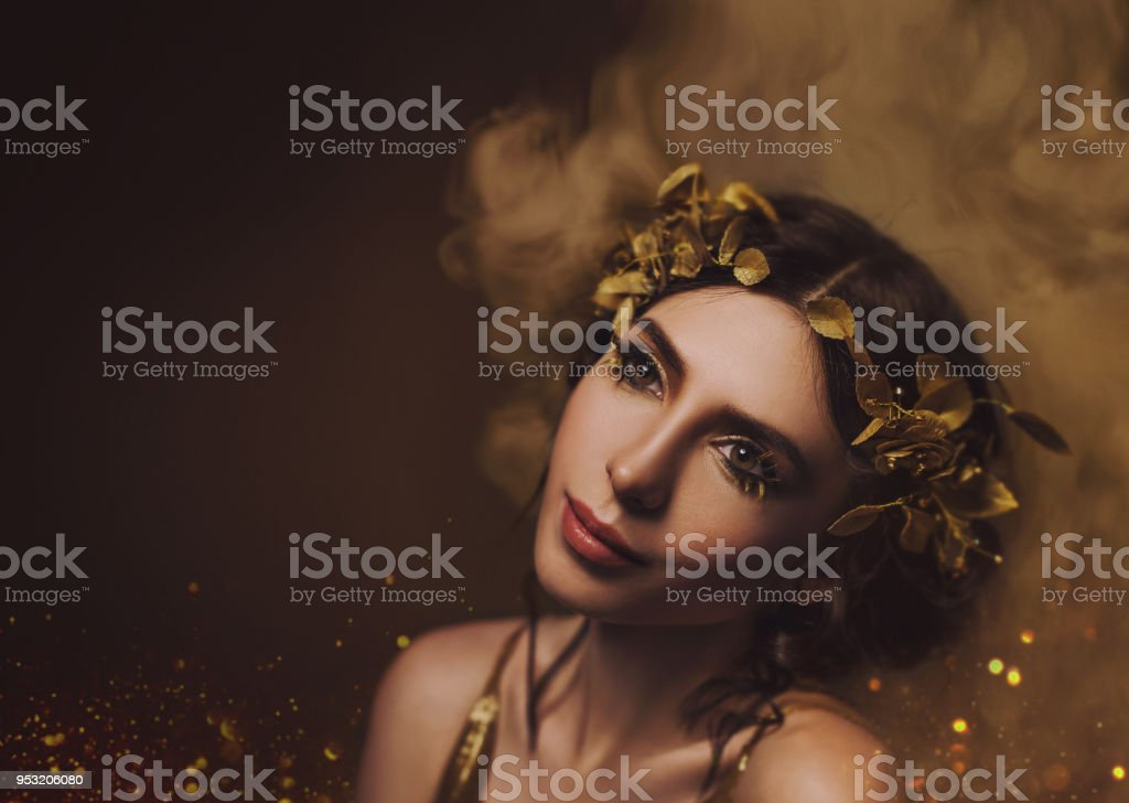 Close-up portrait. Girl with creative make-up and with golden eyelashes. The Greek goddess in a laurel wreath with flowers and handmade roses. Art Photo stock photo