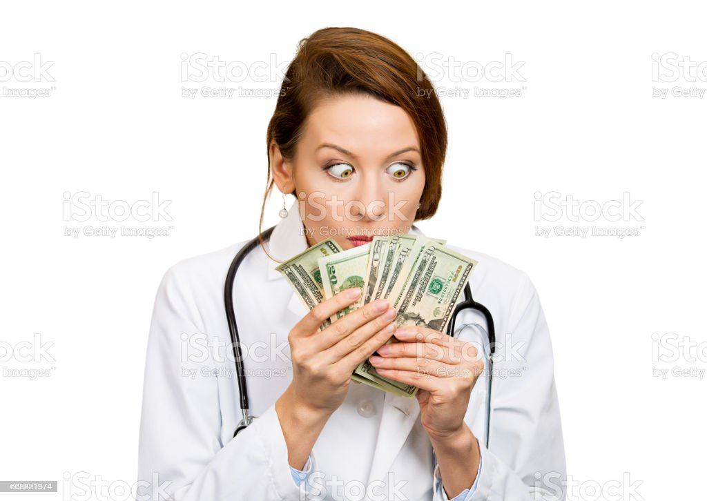 Closeup portrait greedy, miserly health care professional, female doctor holding, looking at her money dollars in hand stock photo