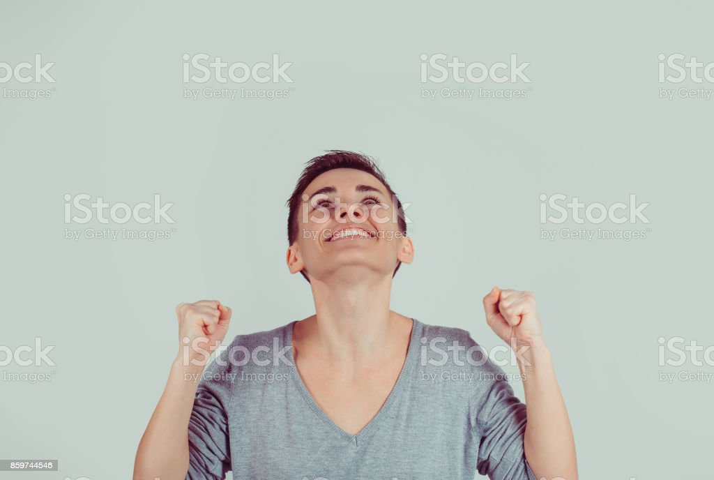 Closeup portrait happy successful student woman winning fists pumped celebrating success isolated light green gray wall background. Positive human emotion facial expression Life perception achievement stock photo