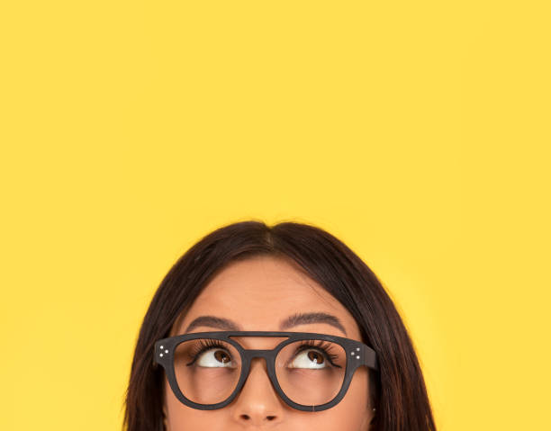 closeup portrait headshot cute happy woman in glasses looking up closeup portrait headshot cropped face above lips of cute happy woman in glasses looking up isolated on yellow studio wall background with copy space above head. Human face expressions, emotions tuinkers stock pictures, royalty-free photos & images