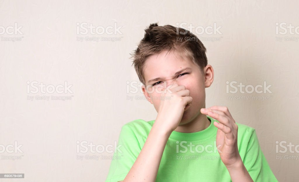 Closeup portrait kid pinches nose with fingers hands looks with disgust something stinks bad smell isolated on white wall background with copyspace. Human face expression body language reaction. stock photo