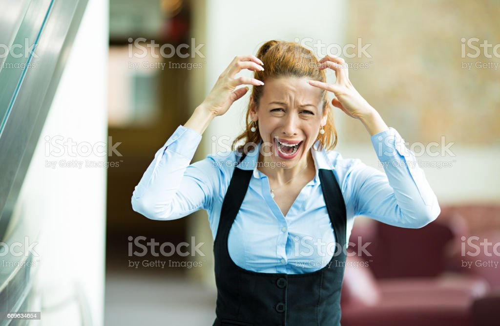 Closeup portrait mad, angry, upset stressed young businesswoman, worker, furious yelling hands in air stock photo