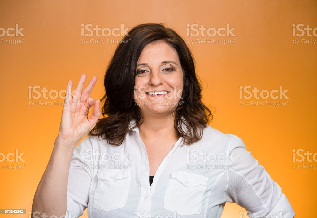 Closeup portrait middle aged happy smiling excited natural woman giving OK sign stock photo