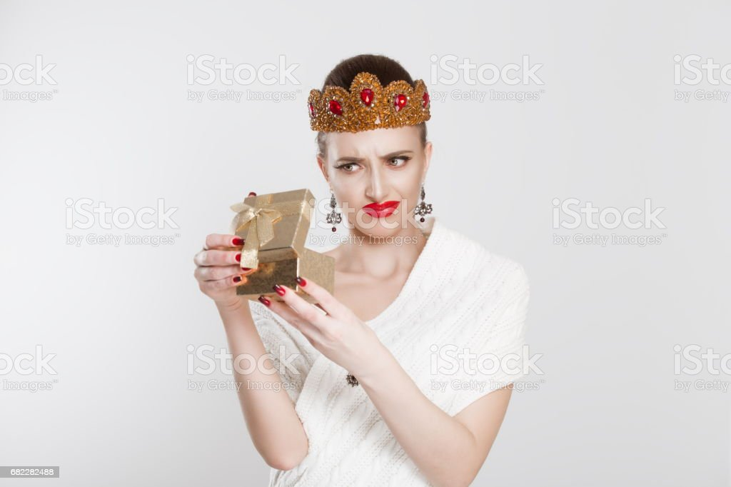 Closeup portrait middle aged woman opening gift box very upset at what she received, isolated white background. Negative human emotion, facial expression. Unsuccessful holiday shopping concept stock photo