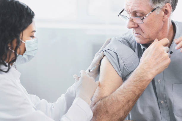 Closeup portrait nurse doing injection to senior man stock photo