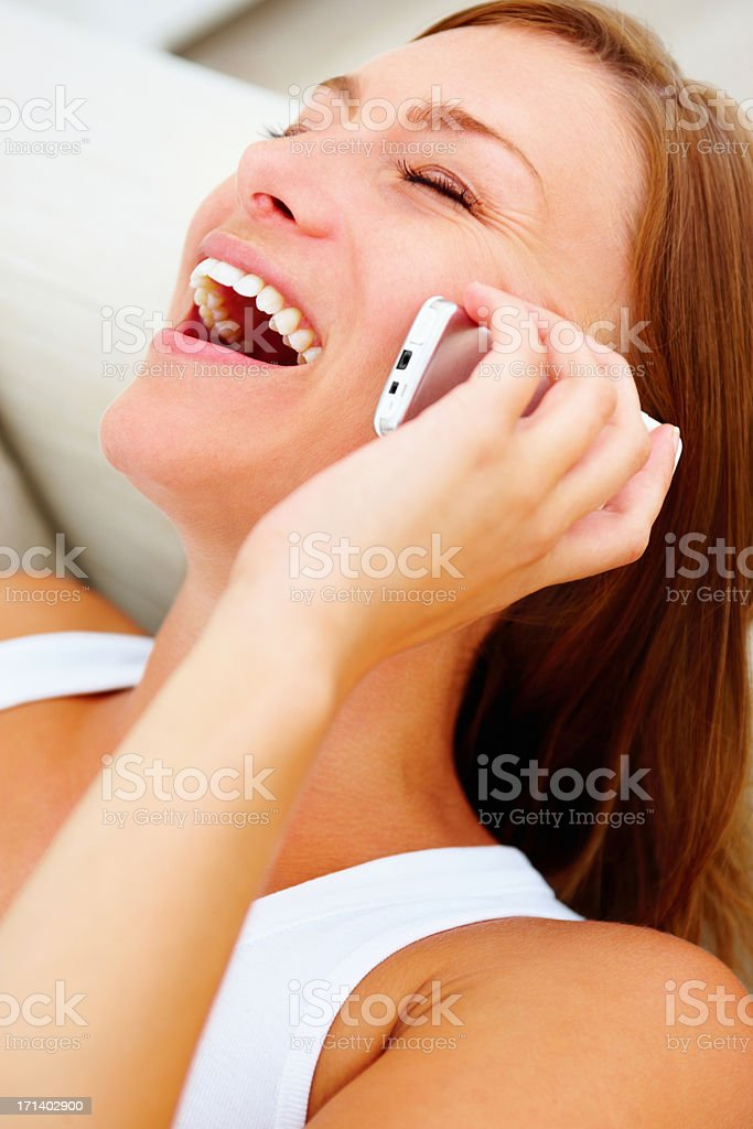 Closeup portrait of a beautiful lady laughing and talking on a cellphone stock photo