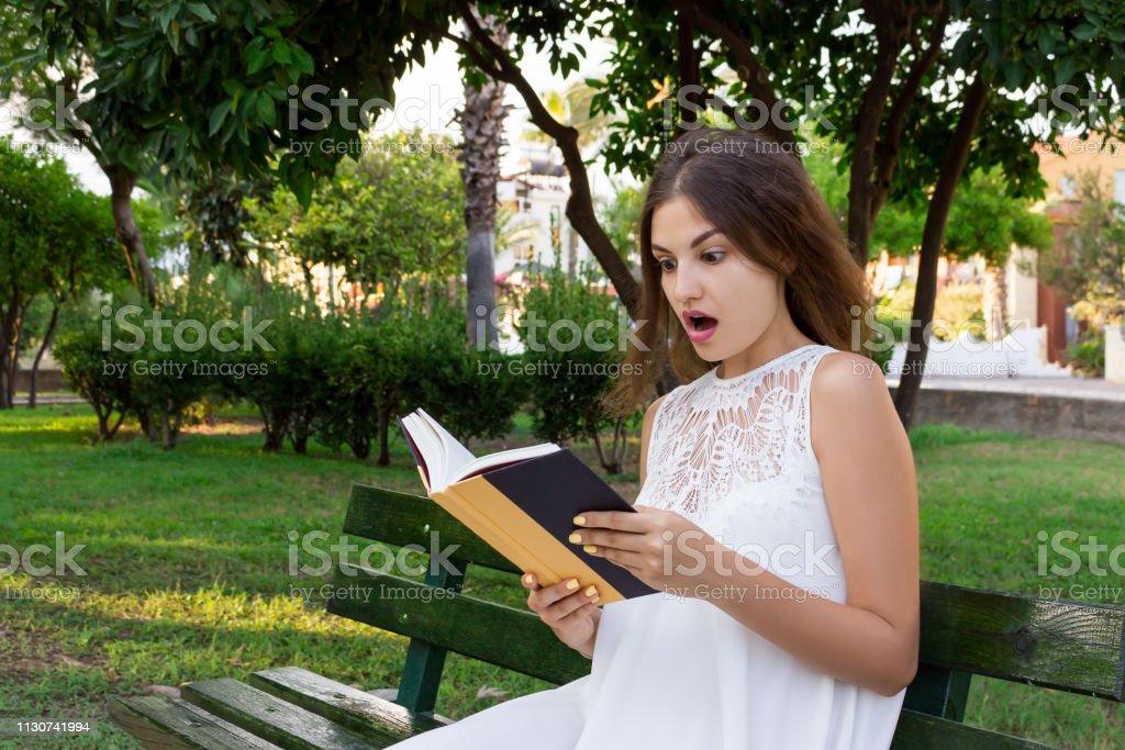 Nahaufnahme Porträt eines schönen überraschten Mädchens mit weit geöffneten Augen, das ein Buch auf der Bank im Park liest. menschlichen Emotionen Mimik Reaktion – Foto