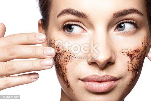 istock Close-up portrait of a beautiful woman with a coffee scrub on her face doing peeling skin isolated on white background 825324532