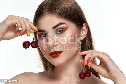 istock Closeup portrait of a beautiful young woman with bright color make-up holding strawberry near the face. 1164263766