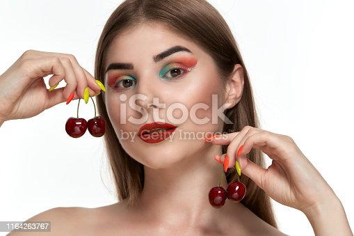 istock Closeup portrait of a beautiful young woman with bright color make-up holding strawberry near the face. 1164263767